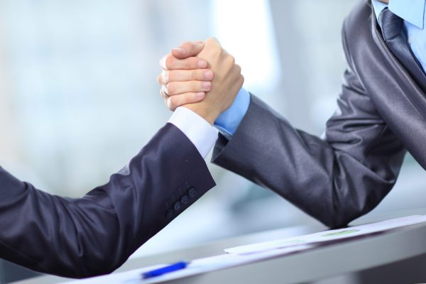 Two businessmen press hands each other on a forward background