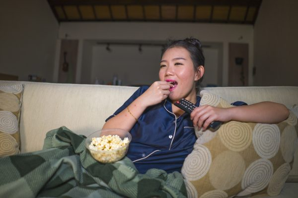 young beautiful happy and relaxed Asian Korean woman at home living room sitting cozy on sofa couch watching TV show episode or romantic comedy movie eating popcorn