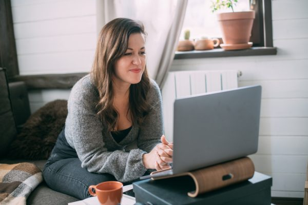 Woman works with laptop at home in the living room