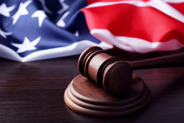 Judge gavel with american flag on wooden table