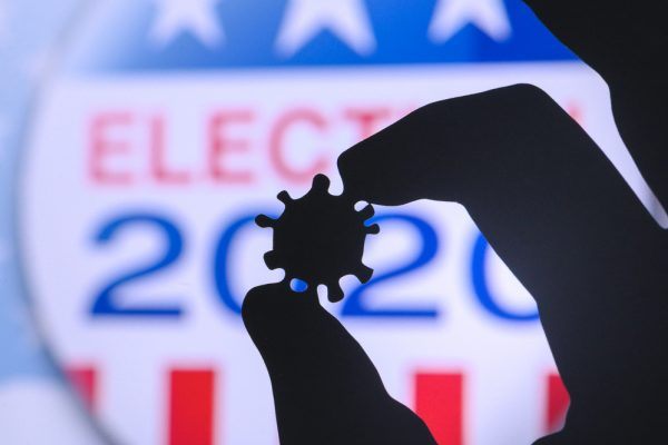 Hand silhouette hold covid 19 virus. Logo of USA presidental Election 2020 in background. US presidential elections are threatened by coronavirus and may be postponed