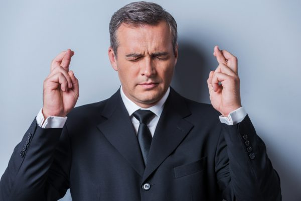 Waiting for special moment. Portrait of mature man in formalwear keeping fingers crossed and eyes closed while standing against grey background