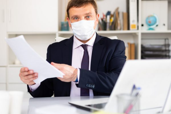 Manager in disposable mask discussing in office
