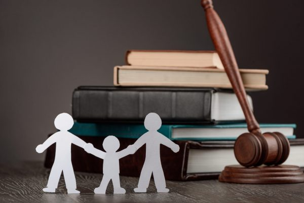 Paper people chain, books and judge's gavel. Law, family politics and gay marriage legalization.