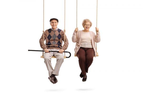 Elderly man and an elderly woman sitting on swings