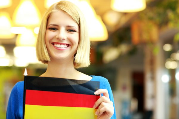 Cheerful blonde girl holding flag of Germani