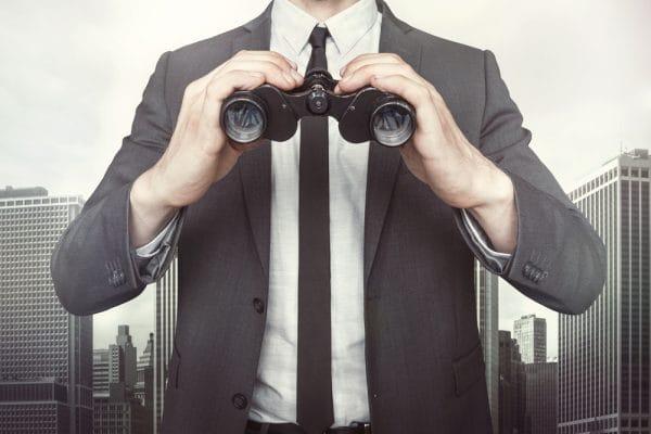 Businessman holding binoculars on cityscape background