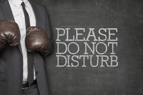 Please do not disturb on blackboard with businessman wearing boxing gloves