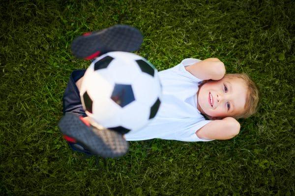 Little Boy practising soccer outdoors