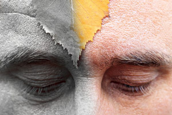 male eyes are looking down at the forehead sheet. half of the image is colored silver. the arrival of oldness is not avoided