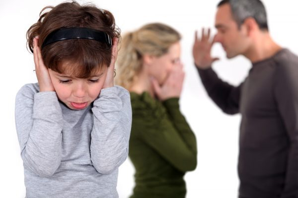 Young girl trying to block out the sound of her parents arguing