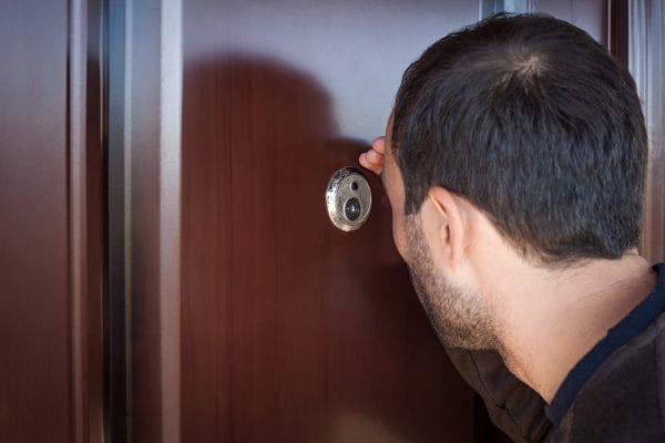 Caucasian man looks through the peephole.